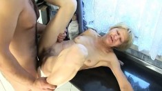 Naughty granny blows and fucks a young stud's cock in the kitchen