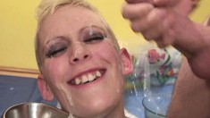 Short-haired blonde works a couple of stiff pricks and gets cum on her face