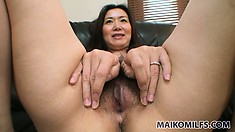 Sultry Asian cougar drops her black dress to reveal her lovely tits and tight peach