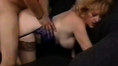 Busty blonde lady blowing and fucking a young stud's dick on the couch